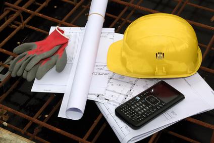 casque de chantier, plans, calculatrice et gants